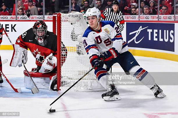 Jack Roslovic of Team United States skates the puck around the net of goaltender Carter Hart of Team Canada during the 2017 IIHF World Junior...