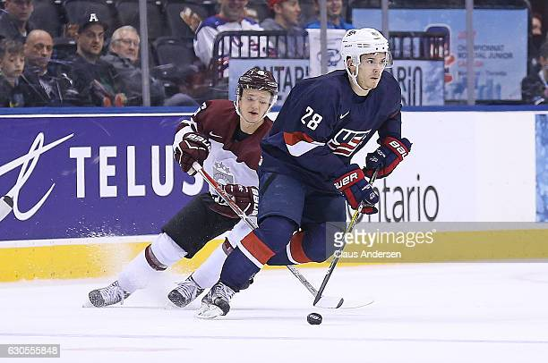 Jack Roslovic of Team USA skates away from a checking Valters Apfelbaums of Team Latvia during a 2017 IIHF World Junior Hockey Championship game at...