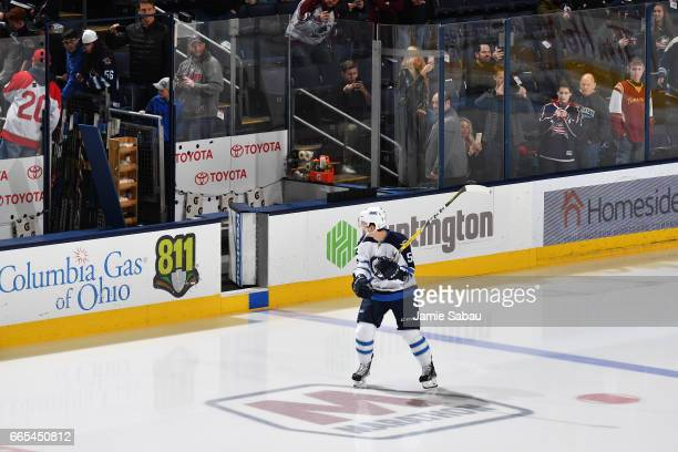 Jack Roslovic of the Winnipeg Jets looks back after being tricked into taking the ice on his own for pregame warmups prior to his NHL debut in a game...
