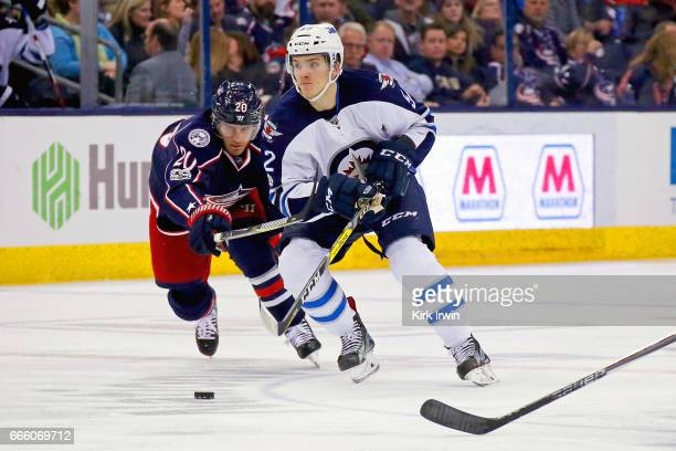 Jack Roslovic of the Winnipeg Jets skates the puck away from Brandon Saad of the Columbus Blue Jackets while making his NHL debut during the game on...