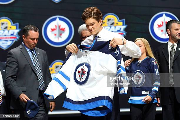 Jack Roslovic puts on his jersey after being selected 25th overall by the Winnipeg Jets in the first round of the 2015 NHL Draft at BBT Center on...