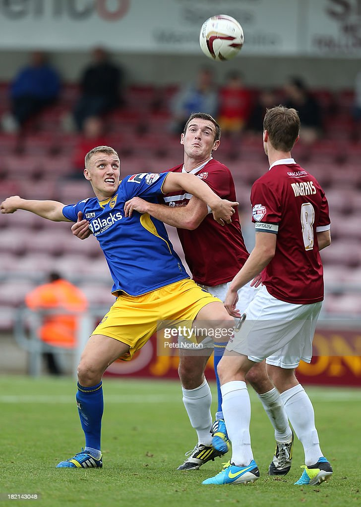 Jack Sampson of Morecambe attempts to control the ball under pressure from Lee Collins of Northampton Town as Ian Morris looks on during the Sky Bet League Two match between Northampton Town and Morecambe at Sixfields Stadium on September 28, 2013 in Northampton, England.
