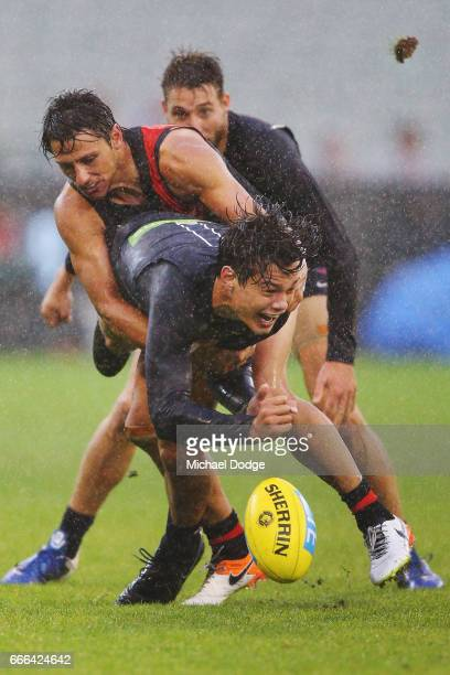 Jack Silvagni of the Blues handballs away from Mark Baguley of the Bombers during the round three AFL match between the Carlton Blues and the...