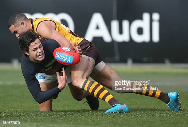 Jack Silvagni of the Blues is tackled by Shaun Burgoyne of the Hawks during the 2016 AFL Round 19 match between the Hawthorn Hawks and the Carlton...