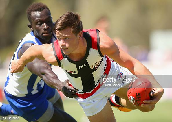 Jack Sinclair of the Saints handballs whilst being tackled by Majak Daw of the Kangaroos during the 2016 AFL NAB Challenge match between the St Kilda...