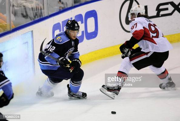 Jack Skille of the Florida Panthers and Matt Gilroy of the Ottawa Senators go after the puck during a NHL game at the BankAtlantic Center on March 4...