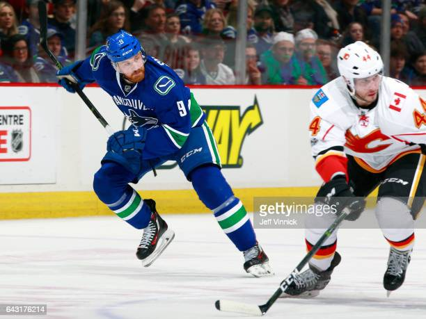 Jack Skille of the Vancouver Canucks and Matt Bartkowski of the Calgary Flames skate up ice during their NHL game at Rogers Arena February 18 2017 in...