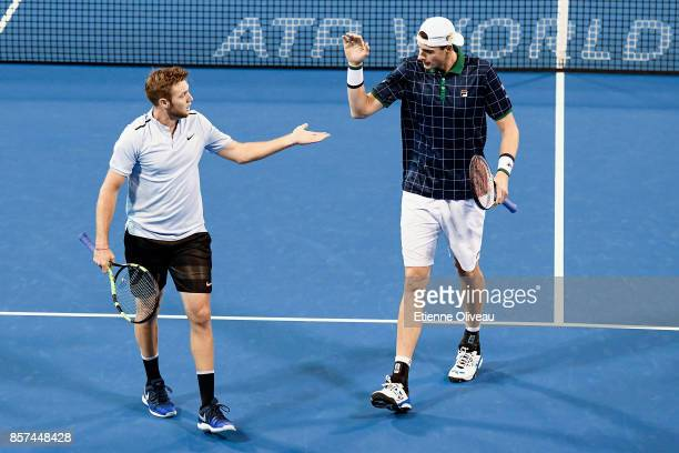 Jack Sock and John Isner of the United States check hands during their Men's double first round match against Lucas Pouille of France and Fernando...