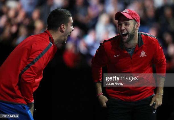 Jack Sock and Thanasi Kokkinakis of Team World react on the players bench as John Isner of Team World plays his singles match against Dominic Thiem...