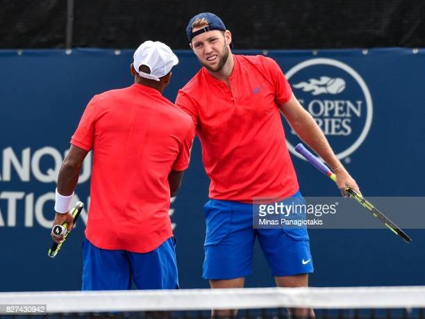 Jack Sock congratulates teammate Nicholas Monroe during their doubles match against Karen Khachanov of Russia and Dominic Thiem of Austria on day...