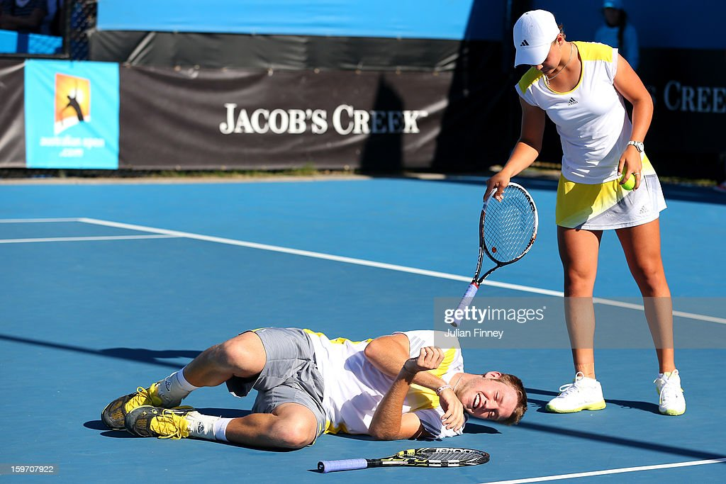 Jack Sock of the United States lies on the court as Ashleigh Barty of Australia watches him in their second round doubles match against Su-Wei Hsieh of Chinese Taipei and Rohan Bopanna of India during day six of the 2013 Australian Open at Melbourne Park on January 19, 2013 in Melbourne, Australia.