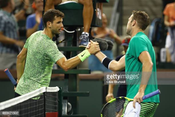 Jack Sock of the United States shakes hands at the net after his three set victory against Grigor Dimitrov of Bulgaria in their third round match...
