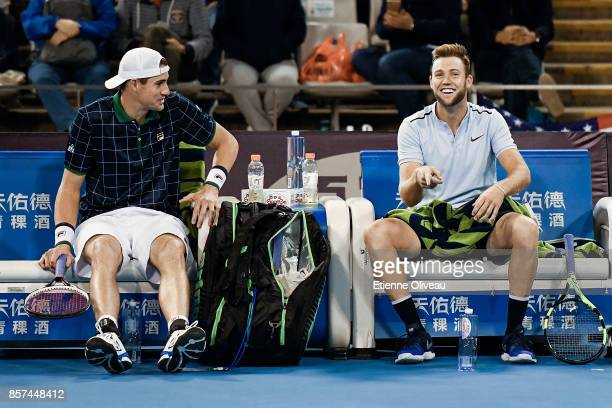 Jack Sock of the United States smiles after flipping his bottle of water while his partner John Isner of the United States looks at him during their...