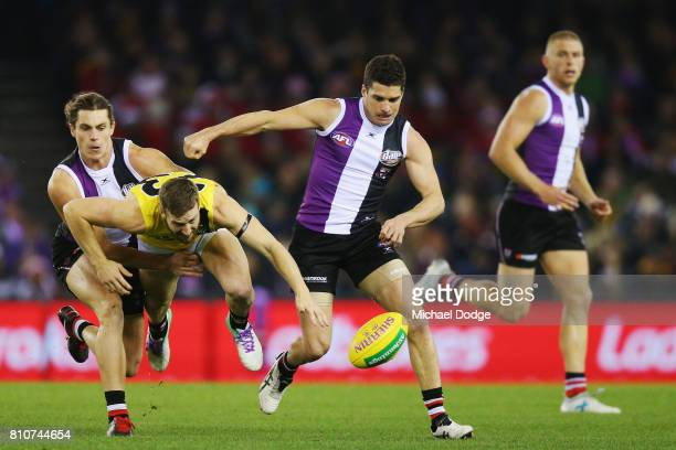 Jack Steele of the Saints and Leigh Montagna of the Saints tackle Kane Lambert of the Tigers during the round 16 AFL match between the St Kilda...