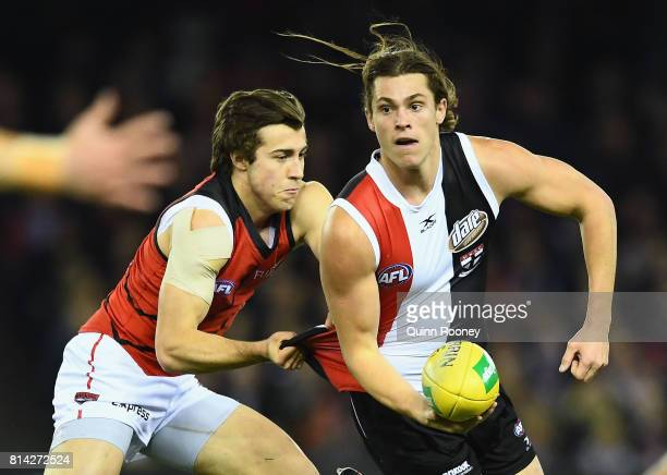 Jack Steele of the Saints handballs whilst being tackled by Andrew McGrath of the Bombers during the round 17 AFL match between the St Kilda Saints...
