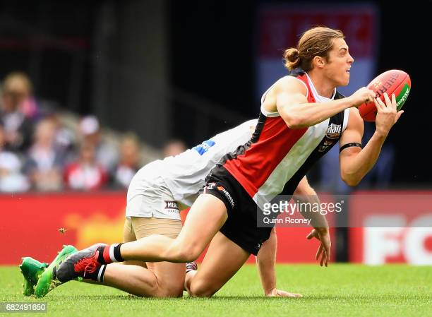 Jack Steele of the Saints handballs whilst being tackled by Bryce Gibbs of the Blues during the round eight AFL match between the St Kilda Saints and...