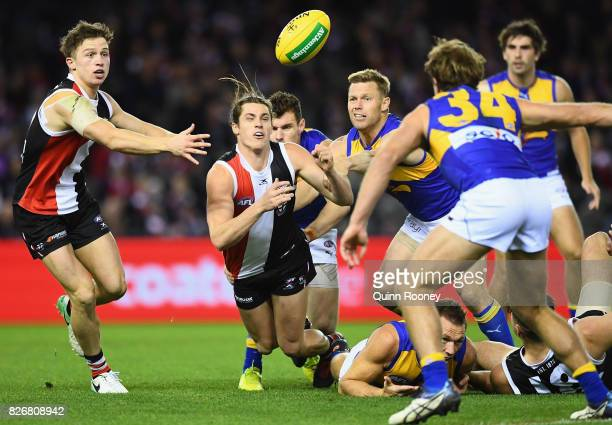Jack Steele of the Saints handballs whilst being tackled by Sam Mitchell of the Eagles during the round 20 AFL match between the St Kilda Saints and...
