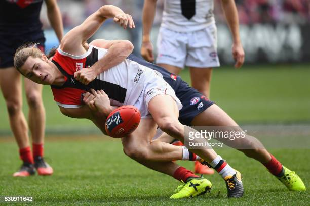 Jack Steele of the Saints is tackled by Michael Hibberd of the Demons during the round 21 AFL match between the Melbourne Demons and the St Kilda...