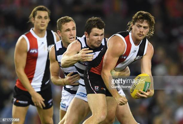 Jack Steven of the Saints handballs whilst being tackled by Patrick Dangerfield of the Cats during the round five AFL match between the St Kilda...