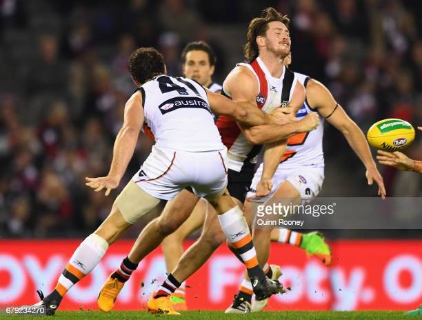 Jack Steven of the Saints handballs whilst being tackled by Shane Mumford of the Giants during the round seven AFL match between the St Kilda Saints...