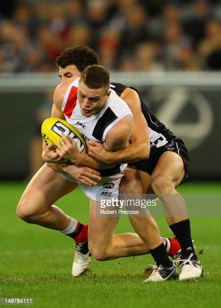 Jack Steven of the Saints is tackled by Alex Fasolo of the Magpies during the round 19 AFL match between the Collingwood Magpies and the St Kilda...