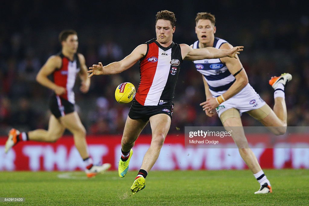 Jack Steven of the Saints runs with the ball away from Mark Blicavs of the Cats during the round 14 AFL match between the St Kilda Saints and the Geelong Cats at Etihad Stadium on June 25, 2016 in Melbourne, Australia.