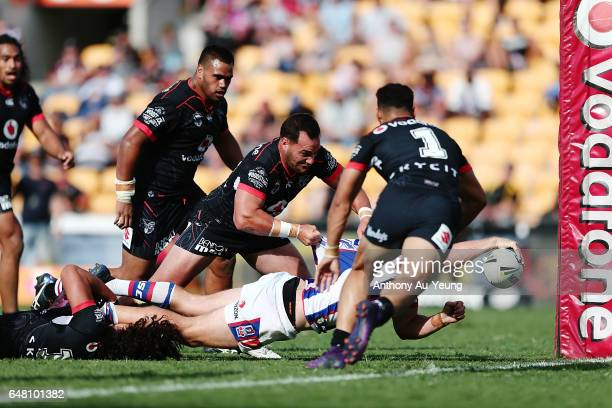 Jack Stockwell of the Knights scores a try against Bodene Thompson of the Warriors during the round one NRL match between the New Zealand Warriors...