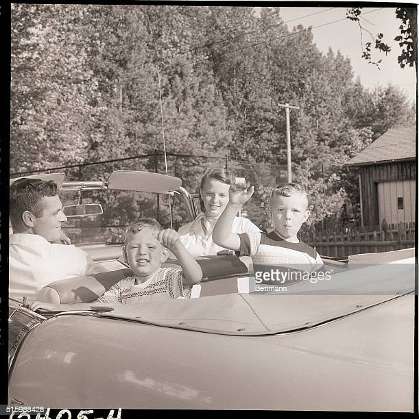 Jack Storey looks around affectionately while driving in order to get a glimpse of his ebullient children Douglas and David Their mother also looks...