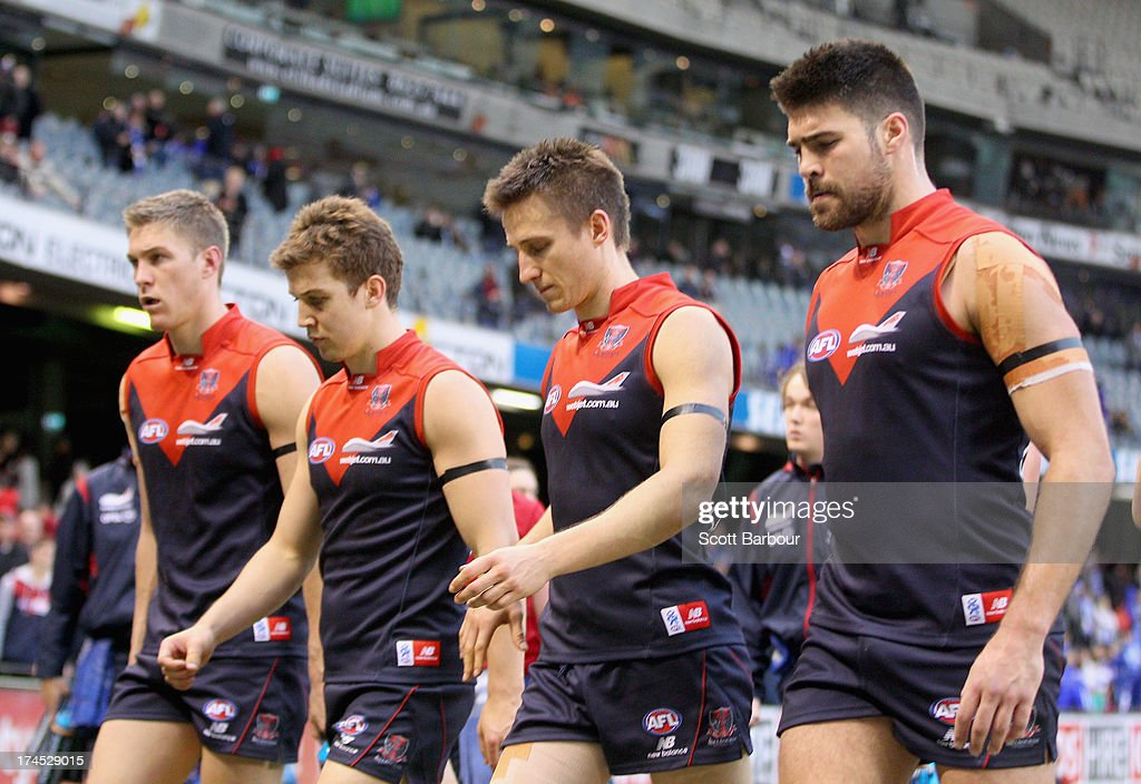 Jack Trengove, Jack Grimes and Chris Dawes of the Demons leave the field after losing the round 18 AFL match between the Melbourne Demons and the North Melbourne Kangaroos at Etihad Stadium on July 27, 2013 in Melbourne, Australia.