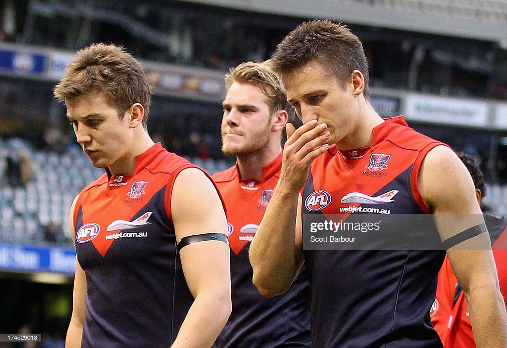Jack Trengove, Jack Grimes and Jack Watts of the Demons leave the field after losing the round 18 AFL match between the Melbourne Demons and the North Melbourne Kangaroos at Etihad Stadium on July 27, 2013 in Melbourne, Australia.