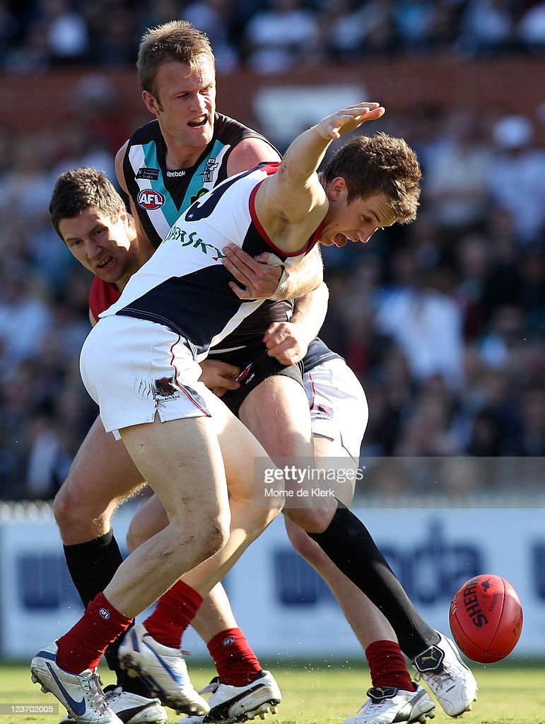 Jack Trengove of the Demons is held back by Dean Brogan of the Power during the round 24 AFL match between the Port Adelaide Power and the Melbourne...