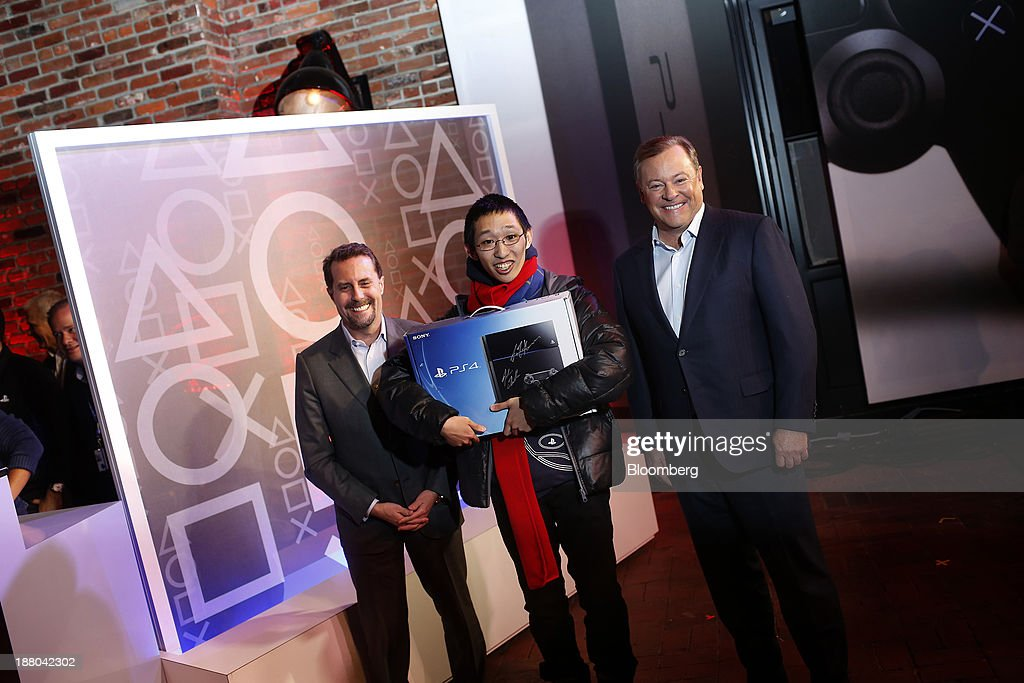Jack Tretton, president and chief executive officer of Sony Computer Entertainment America LLC, right, and Andrew House, president and group chief executive officer of Sony Computer Entertainment Inc., left, pose for a photograph with Joey Chiu, 24, after handing out the first Sony PlayStation 4 console during its midnight launch event in New York, U.S., on Friday, Nov. 15, 2013. Sony Corp., poised to release the PlayStation 4 game console this week, is confident it can meet analysts' sales estimates of 3 million units by year-end, exploiting an early advantage over Microsoft Corp.'s Xbox One. Photographer: Victor J. Blue/Bloomberg via Getty Images