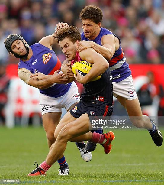 Jack Viney of the Demons fends off Caleb Daniel and Tom Liberatore of the Bulldogs during the 2016 AFL Round 08 match between the Melbourne Demons...