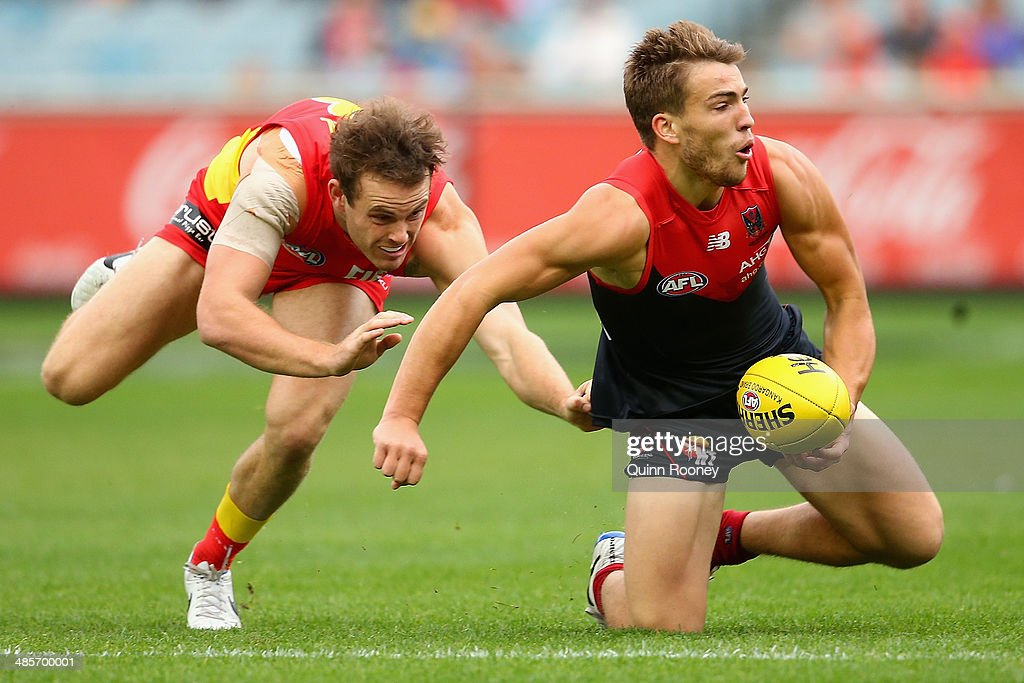 <a gi-track='captionPersonalityLinkClicked' href=/galleries/search?phrase=Jack+Viney&family=editorial&specificpeople=8280691 ng-click='$event.stopPropagation()'>Jack Viney</a> of the Demons handballs whilst being tackled by Luke Russell of the Suns during the round five AFL match between the Melbourne Demons and the Gold Coast Suns at Melbourne Cricket Ground on April 20, 2014 in Melbourne, Australia.