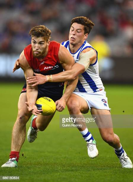 Jack Viney of the Demons handballs whilst being tackled by Nathan Hrovat of the Kangaroos during the round nine AFL match between the Melbourne...