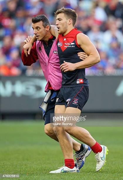 Jack Viney of the Demons is helped off the ground by trainers after a heavy bump with Tim Broomhead of the Magpies during the round 10 AFL match...