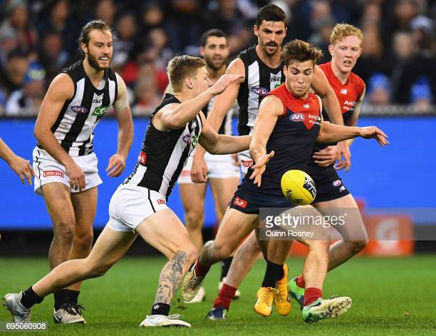 Jack Viney of the Demons kicks whilst being tackled by Jordan DeGoey of the Magpies during the round 12 AFL match between the Melbourne Demons and...