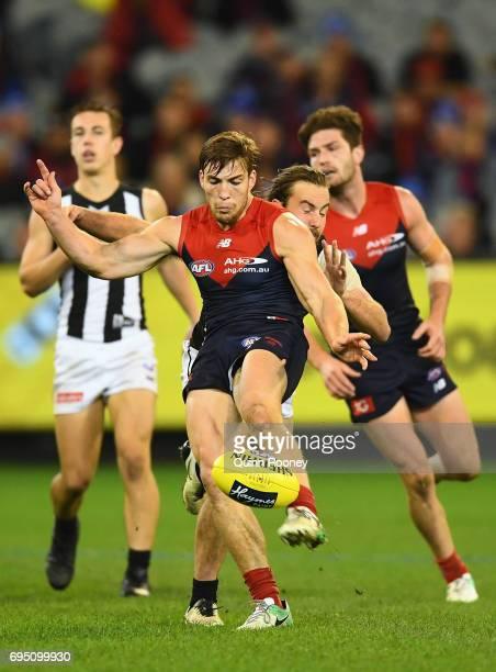 Jack Viney of the Demons kicks whilst being tackled by Tim Broomhead of the Magpies during the round 12 AFL match between the Melbourne Demons and...