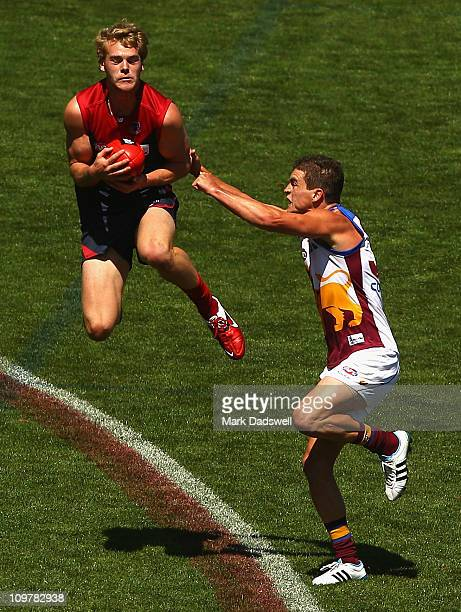 Jack Watts of the Demons flies for a mark over Tom Rockliff of the Lions during the NAB Challenge Cup match between the Melbourne Demons and the...
