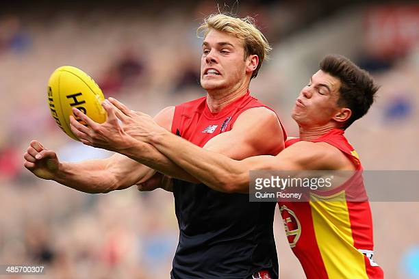 Jack Watts of the Demons handballs whilst being tackled byJaeger O'Meara of the Suns during the round five AFL match between the Melbourne Demons and...