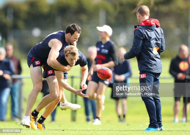 Jack Watts of the Demons passes the ball to Simon Goodwin coach of the Demons as he is tackled by Cameron Pedersen of the Demons during a Melbourne...