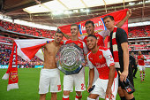Jack Wilshere Calum Chambers Olivier Giroud Alex OxladeChamberlain and Wojciech Szczesny of Arsenal pose with the FA Community Shield during the FA...