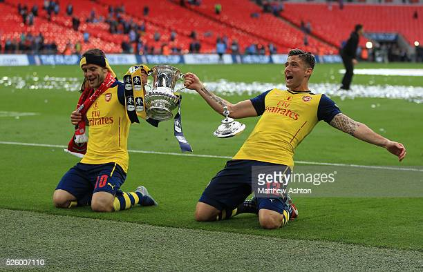 Jack Wilshere of Arsenal and Olivier Giroud of Arsenal slide on their knees with the FA Cup trophy