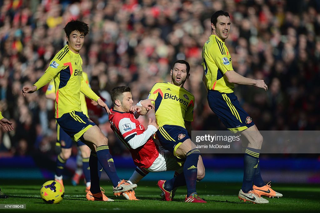 Jack Wilshere of Arsenal battles with Ki Sung-Yueng; Phil Bardsley and John O,Shea of Sunderland during the Barclays Premier League match between Arsenal and Sunderland at Emirates Stadium on February 22, 2014 in London, England.