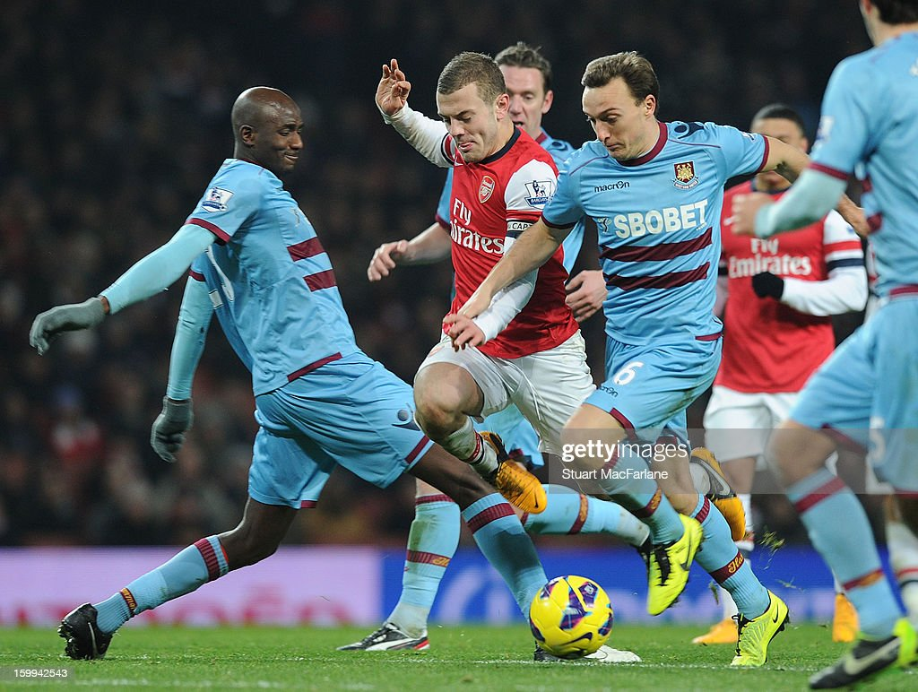<a gi-track='captionPersonalityLinkClicked' href=/galleries/search?phrase=Jack+Wilshere&family=editorial&specificpeople=5446655 ng-click='$event.stopPropagation()'>Jack Wilshere</a> of Arsenal breaks from <a gi-track='captionPersonalityLinkClicked' href=/galleries/search?phrase=Alou+Diarra&family=editorial&specificpeople=465019 ng-click='$event.stopPropagation()'>Alou Diarra</a> and <a gi-track='captionPersonalityLinkClicked' href=/galleries/search?phrase=Mark+Noble&family=editorial&specificpeople=844055 ng-click='$event.stopPropagation()'>Mark Noble</a> of West Ham during the Barclays Premier League match between Arsenal and West Ham United at Emirates Stadium on January 23, 2013 in London, England.
