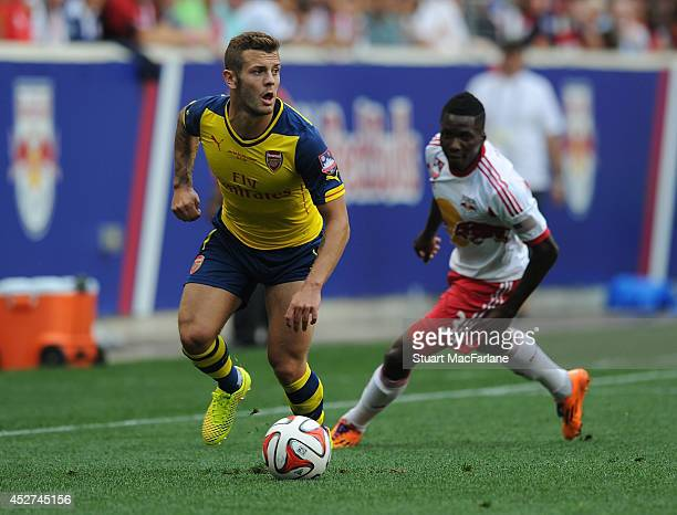Jack Wilshere of Arsenal breaks past Ambroise Oyongo of the Red Bulls during the match between New York Red Bulls and Arsenal at the Red Bull Arena...