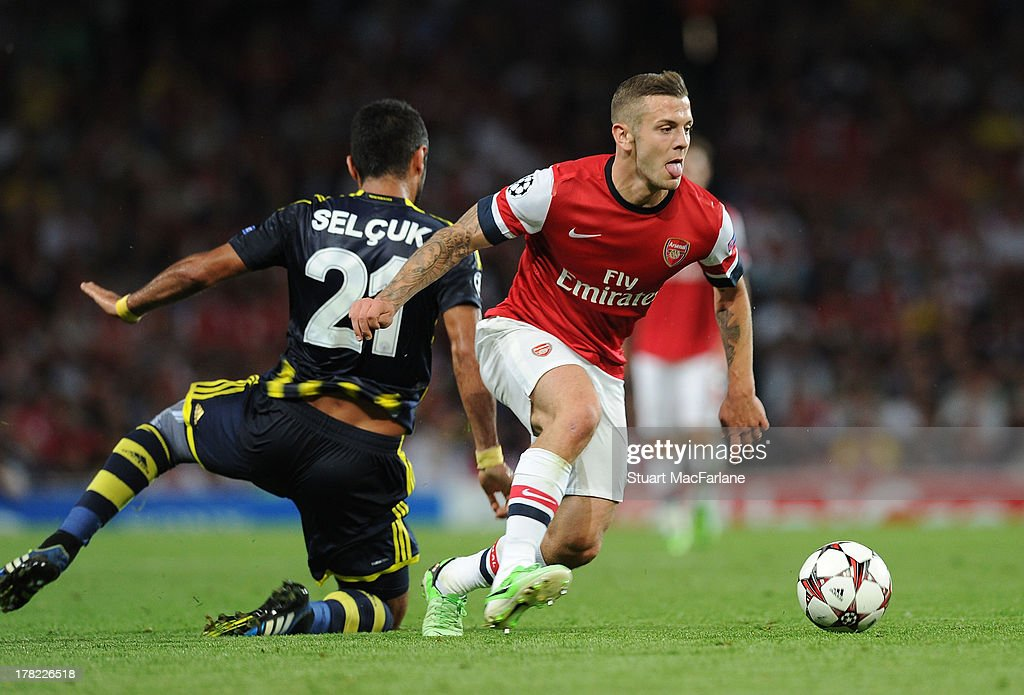 Jack Wilshere of Arsenal breaks past Selcuk Sahin of Fenerbahce during the UEFA Champions League Play Off Second leg match between Arsenal FC and Fenerbahce SK at Emirates Stadium on August 27, 2013 in London, England.