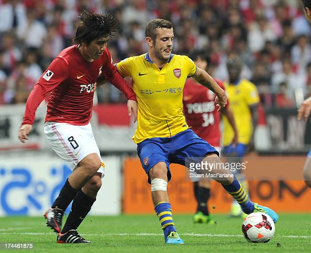 Jack Wilshere of Arsenal breaks past Yosuke Kashiwagi of Urwa during the preseason Asian Tour friendly match between Urawa Red Diamonds and Arsenal...