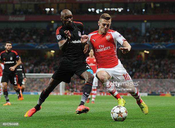 Jack Wilshere of Arsenal challenged by Atiba Hutchinson of Besiktas during the UEFA Play Off match between Arsenal and Besiktas at Emirates Stadium...