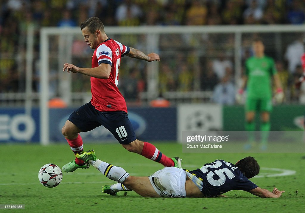 <a gi-track='captionPersonalityLinkClicked' href=/galleries/search?phrase=Jack+Wilshere&family=editorial&specificpeople=5446655 ng-click='$event.stopPropagation()'>Jack Wilshere</a> of Arsenal challenged by <a gi-track='captionPersonalityLinkClicked' href=/galleries/search?phrase=Emre+Belozoglu&family=editorial&specificpeople=649491 ng-click='$event.stopPropagation()'>Emre Belozoglu</a> of Fenerbache during the UEFA Champions League Play Off first leg match between Fenerbache SK and Arsenal FC at sukru Saracoglu Stadium on August 21, 2013 in Istanbul, Turkey.